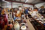 People viewing lots for sale inside auction room at Camps Ashe, Suffolk, England