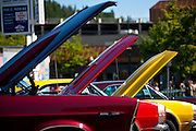 BEN BREWER/Press A 1966 Ford Galaxy, left, props its hood open next to two 1967 Chevrolet Camaros along Second Street during Car d'Lane on Saturday afternoon.