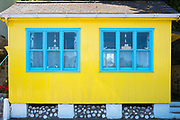 Bright yellow and blue painted beach hut seaside home in the resort of Rozel in St Martin region of Jersey, Channel Isles