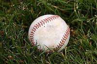 28 April 2007:Detail photo of baseball sitting in green grass.  Newport Coast youth t-ball baseball league in CA.