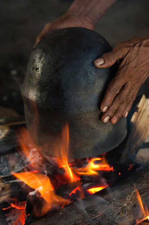 Huaorani Indian clay pot being dryed on the fire after use. Gabaro Community. Yasuni National Park.<br /> Amazon rainforest, ECUADOR.  South America<br /> They have a unique style of pots not seen amoung the other Indian tribes in Ecuador<br /> This Indian tribe were basically uncontacted until 1956 when missionaries from the Summer Institute of Linguistics made contact with them. However there are still some groups from the tribe that remain uncontacted.  They are known as the Tagaeri. Traditionally these Indians were very hostile and killed many people who tried to enter into their territory. Their territory is in the Yasuni National Park which is now also being exploited for oil.