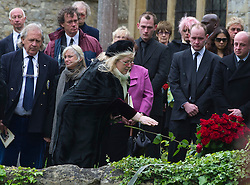 © London News Pictures. 08/06/2012. Thame, UK.  Dwina Gibb, wife of Robin Gibb throwing a rose on to the coffin of her husband Robin Gibb during a burial at St Mary's Church in Thame, Oxfordshire  on June 8, 2012. Robin Gibb died on May 20, 2012 aged 62 following a long battle against cancer. Photo credit: Ben Cawthra/LNP