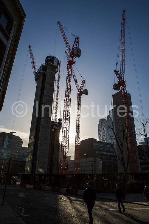 Red construction cranes are silhouetted by the sun on a Mace construction site, Broadgate, next to Liverpool Street station, London, United Kingdom.
