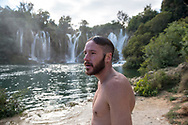 As a light rain falls, a young Australian man backpacking in eastern Europe stands after a swim at Kravice Falls, located about 40 kilometers from Mostar, in Bosnia and Herzegovina.