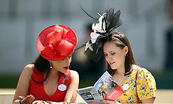 Female racegoers read the programme during day three of Royal Ascot at Ascot Racecourse.