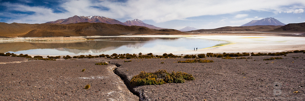 Two people walk on the basalt shore of one of many lakes in the Eduardo Avaroa Andean Fauna National Reserve where a volcano reflects off the water in this two image panoramic.