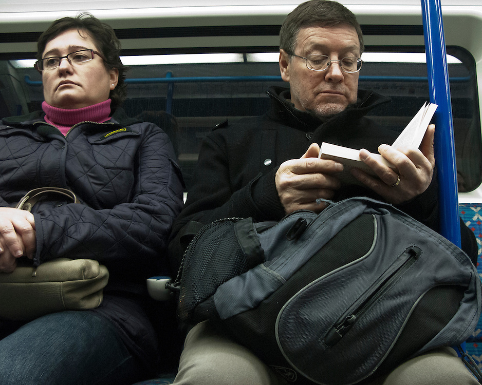 Londoners travelling on the Underground Network reading a book