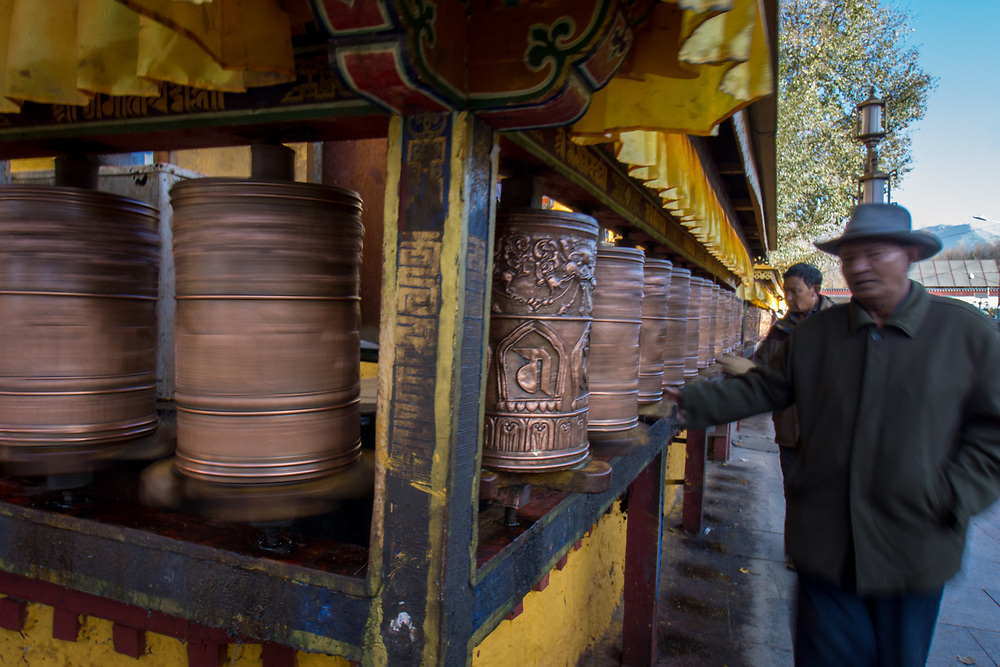 In Tibet the spiritual elements associated with the practice of spinning the prayer wheels was fascinating.  I took this picture while watching one of the pilgrims doing his round on a chilly morning with one hand on the wheel and the other is warm in his pocket.