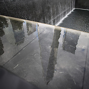 The One World Trade Center reflected in the water of the National September 11 Memorial in Downtown Manhattan, New York City, USA. 16th September 2014. Photo Tim Clayton