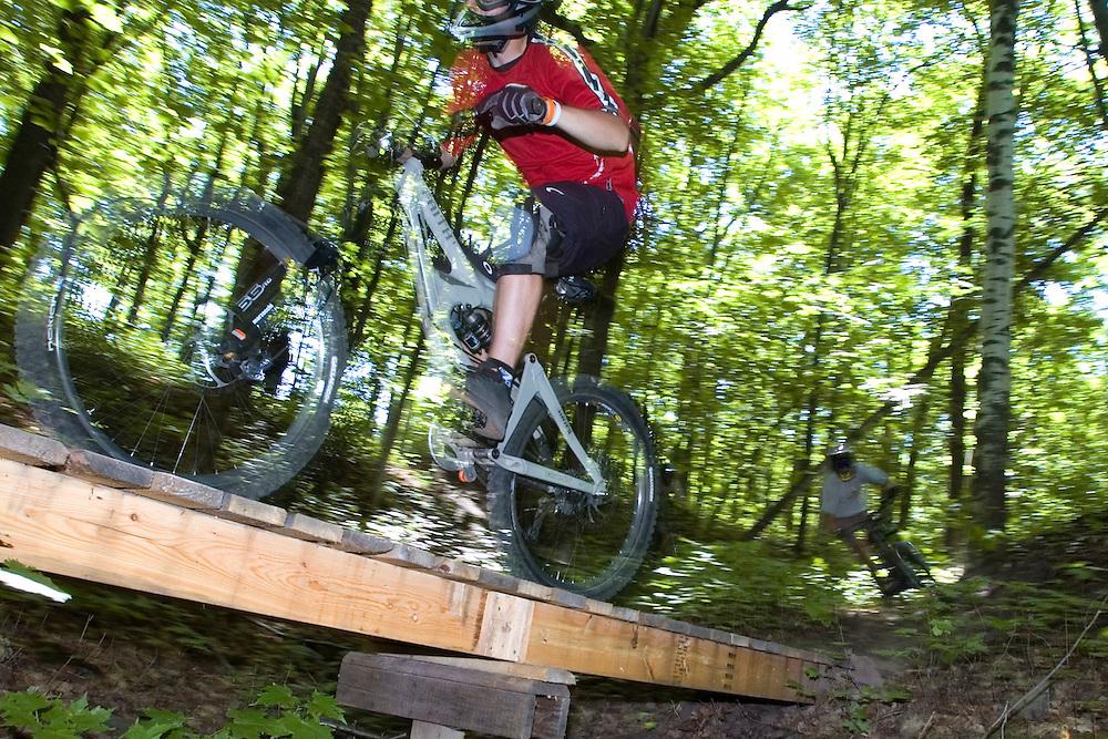 Mountain bikers cross a wooden bridge while freeriding near Marquette Michigan.