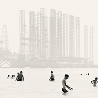 USE ARROWS ← → on your keyboard to navigate this slide-show<br /> <br /> Baku, Azerbaijan, 24 July 2012<br /> Azeri people swim beside an oil extraction platform in Baku.<br /> Photo: Ezequiel Scagnetti