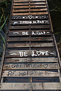 """Salt Spring Island has a population of people who could be described as """"Hippies"""".  This writing was on the improvised walkway consisting of warehouse pallets between the shore and the dock at Blackburn Lake.  This dock is a clothing optional area at Blackburn Lake between Ganges and Fulford Harbour on Salt Spring Island, British Columbia, Canada."""