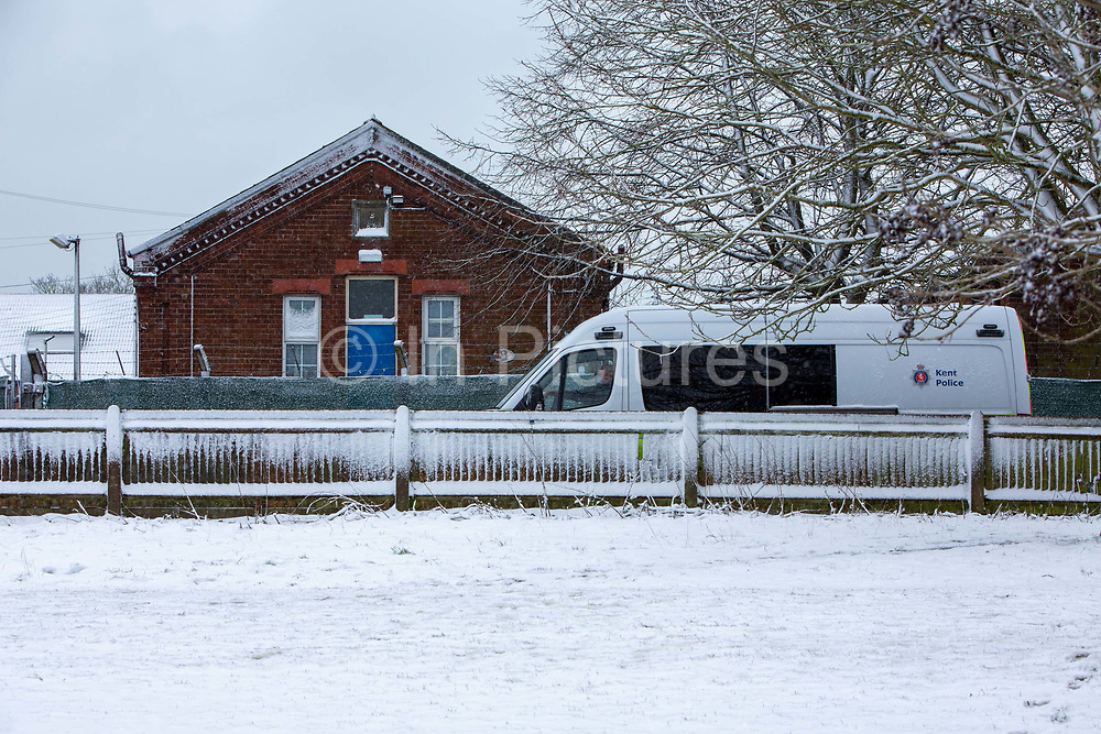 A Police van stationed outside Napier Barracks in the snow, on the 7th of February 2021, Folkestone, United Kingdom. The police have been forcing anyone who leaves back inside Napier Barracks due to COVID-19 restrictions, sometimes even carrying them back through the gates.Over 400 asylum seekers are being kept at Napier Barracks in unsuitable, cold accommodation, they are experiencing mental health issues as well as being vulnerable to health conditions including COVID-19. 3 people living inside the barracks have attempted suicide in 2021 already.