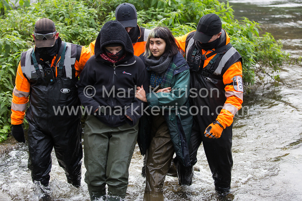 Denham, UK. 5th November, 2020. HS2 security guards push female anti-HS2 activists in the river Colne at Denham Ford during bridge building works for the HS2 high-speed rail link on the first day of the second national coronavirus lockdown. Prime Minister Boris Johnson has advised that construction work may continue during the second lockdown but those working on construction projects are required to adhere to Site Operating Procedures including social distancing guidelines to help prevent the spread of COVID-19.