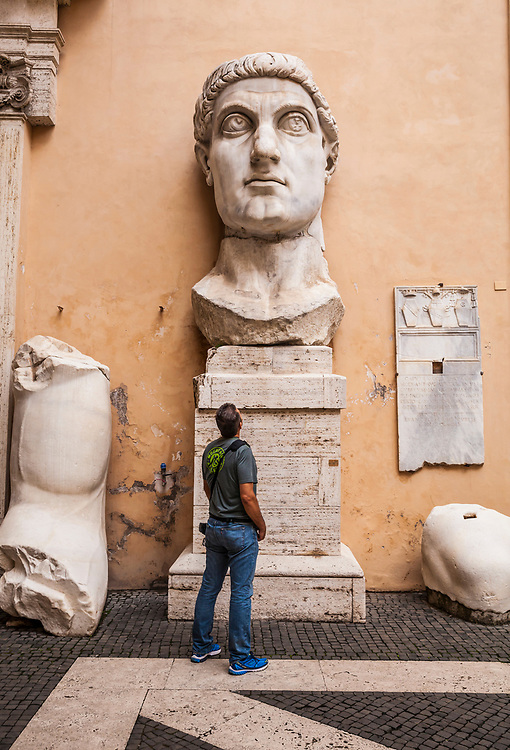 The fragments and head of the colossal statue of Constantine with a man standing below looking up at it. Capitoline Museum, Rome Italy.