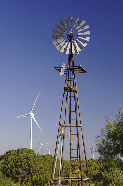 Merkel, TX October 4, 2006: An old water well sits in front of modern wind turbines at the  Buffalo Gap Wind Power project in Taylor and Nolan counties just south of Abilene.  ©Bob Daemmrich /