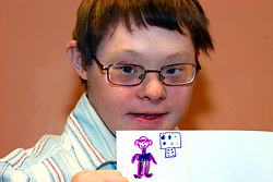 Young man with Downs Syndrome at a support group for people with learning disabilities holding up his self portrait UK