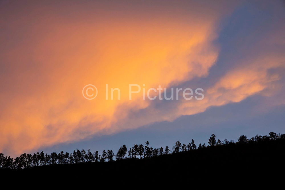 Orange clouds glow over the tree line on top of the hill above the village on the 3rd of March 2020 in Raniswara, Ghairung, Gorkha, Nepal.