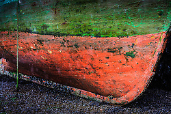 Red and green painted hull of boat in harbor at low tide, Kinvarra, County Galway, Ireland