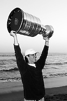 24 August  2002: Detroit Red Wings professional hockey player  Luc Robitaille holds the NHL Stanley Cup over his head at sunset on the beach at the Pacific Ocean in Malibu. .