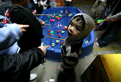 03 Feb 2006. East New Orleans, Louisiana.<br />  Tet, or Tet Nguyen Dan, Vietnamese Lunar New Year. Year of the Dog celebrations amongst the Vietnamese community of East Orleans. Children and their parents hook fish from a pool winning prizes like inflatable Nemos hanging from the fairground like attraction. A young boy takes advice from his father.<br /> Photo; Charlie Varley/varleypix.com