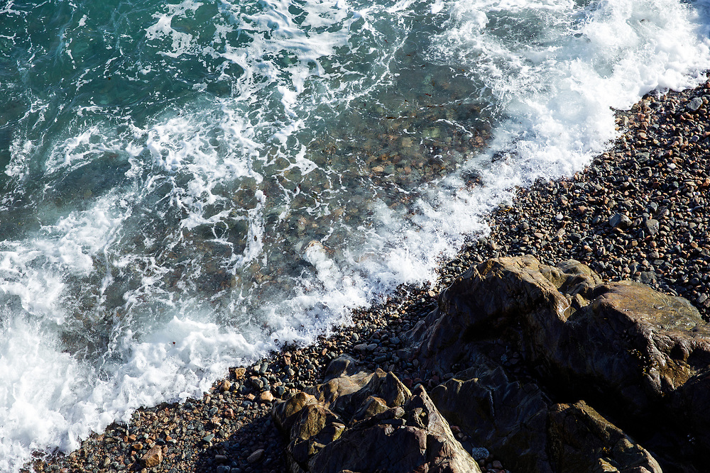 Crystal clear water lapping the shoreline over pebbles and rocks on the beach at St Peter Port, Guernsey, Channel Islands