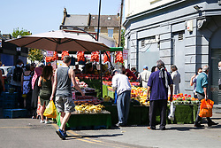 © Licensed to London News Pictures. 30/05/2020. London, UK. Members of the public at a fruit and vegetables outdoors stall in Wood Green, north London. The government has announced a relaxing of COVID-19 lockdown rules from Monday 1 June. Photo credit: Dinendra Haria/LNP