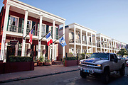US, French, and Louisiana flags seen flying outside a row of traditional buildings, New Orleans, Louisiana, USA.