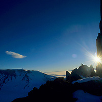 ANTARCTICA, Queen Maud Land. Midnight sun creeps around southeast ridge of the Troll's Castle, Filchner Mts.