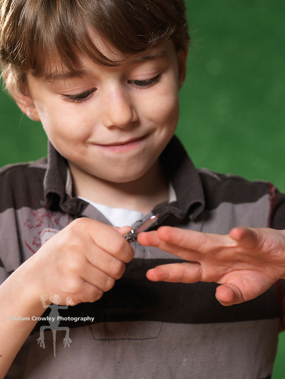 Portrait of boy (7 years old) trims his nails with a nail clipper.