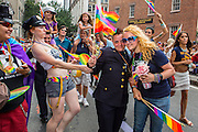 A uniformed member of the New York Police Department's Gay Officers' Action League waves a rainbow flag on Christopher Street as she is cheered by well-wishers.