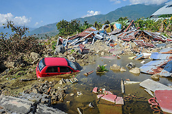 October 3, 2018 - Palu, Central Sulawesi, Indonesia - A damaged vehicle is seen between Balaroa village ruins after the earthquake in Palu. A deadly earthquake measuring 7.7 magnitude and the tsunami wave caused by it has destroyed the city of Palu and much of the area in Central Sulawesi. According to the officials, death toll from devastating quake and tsunami rises to 1,347, around 800 people in hospitals are seriously injured and some 62,000 people have been displaced in 24 camps around the region. (Credit Image: © Hariandi Hafid/SOPA Images via ZUMA Wire)