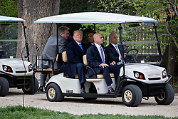 U.S. President Donald Trump, center left, and Emmanuel Macron, France's president, center, sit in a golf cart while touring outside the Mansion at the Mount Vernon estate of first U.S. President George Washington in Mount Vernon, Virginia, U.S., on Monday, April 23, 2018. As Macron arrives for the first state visit of Trump's presidency, the U.S. leader is threatening to upend the global trading system with tariffs on China, maybe Europe too. Photographer: Andrew Harrer/Bloomberg