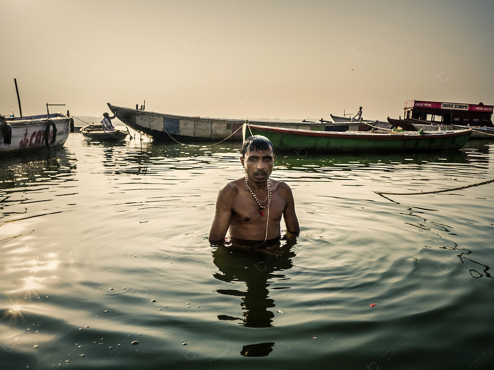 Varanasi, India - October 08, 2015 Pilgrim bathing in the Ganges river at sunrise. The river is considered holy by Hindus. It is venerated as Goddess Ganga and bathing in their waters is considered a ritual that offers respect to the Goddess and internal purification. If this ritual is done in Varanasi it is even more powerful as this is the holiest city of the Jain and Hindu religion.