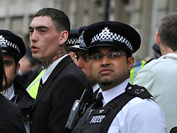 © Licensed to London News Pictures. 11/11/2011. London, UK. A police officer stands next to an arrested man. Police arrest members of the EDL near the Cenotaph following a Remembrance Day service today (11/11/2011). A large group of EDL members where arrested. Police a. Photo credit : Stephen Simpson/LNP