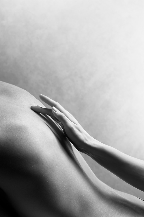 Black and white photo of woman's graceful hand caressing man's back