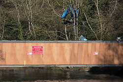 Denham, UK. 13th February, 2021. A view of a temporary Bailey bridge across the river Colne at Denham Ford to be used by contractors working on behalf of HS2 Ltd to relocate a pylon in Denham Country Park. A protest camp occupied by activists opposed to the HS2 high-speed rail project from HS2 Rebellion is located behind the bridge on the far bank of the river.