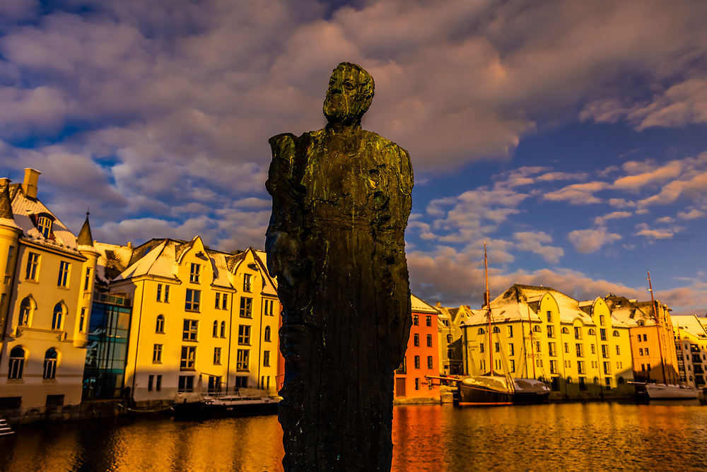 Bronze statue of Harald Grytten  (by artist Leon Roald) with beautiful former warehouses along the canal in the Brosundet quarter  behind, in Art Nouveau (Jugendstil) architectural style, Alesund, Norway. Most of the town was rebuilt after a fire in 1904, with the help of Kaiser Wilhelm of Germany, who often vacationed in the area.