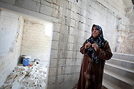 A resident of al-Basheria, Idlib province, describes how her house was partly destroyed in an attack perpertrated by the Syrian military, in which her son was killed on April 22nd 2012. Basheria, Idlib, Syria. 14/06/2012