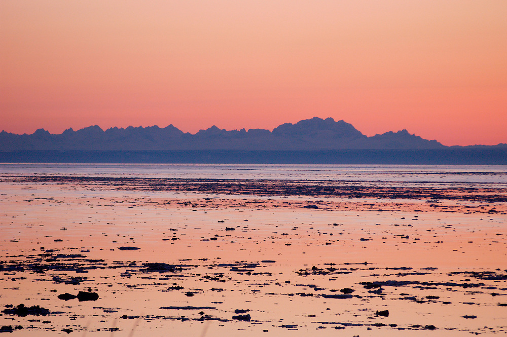 Alaska. USA. Cook Inlet. Point Woronzoff and the Alaska Range at sunset with tidal change and icebergs. Tordrillo Mountains in the distance.