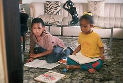 Small children watching tv whilst doing their homework