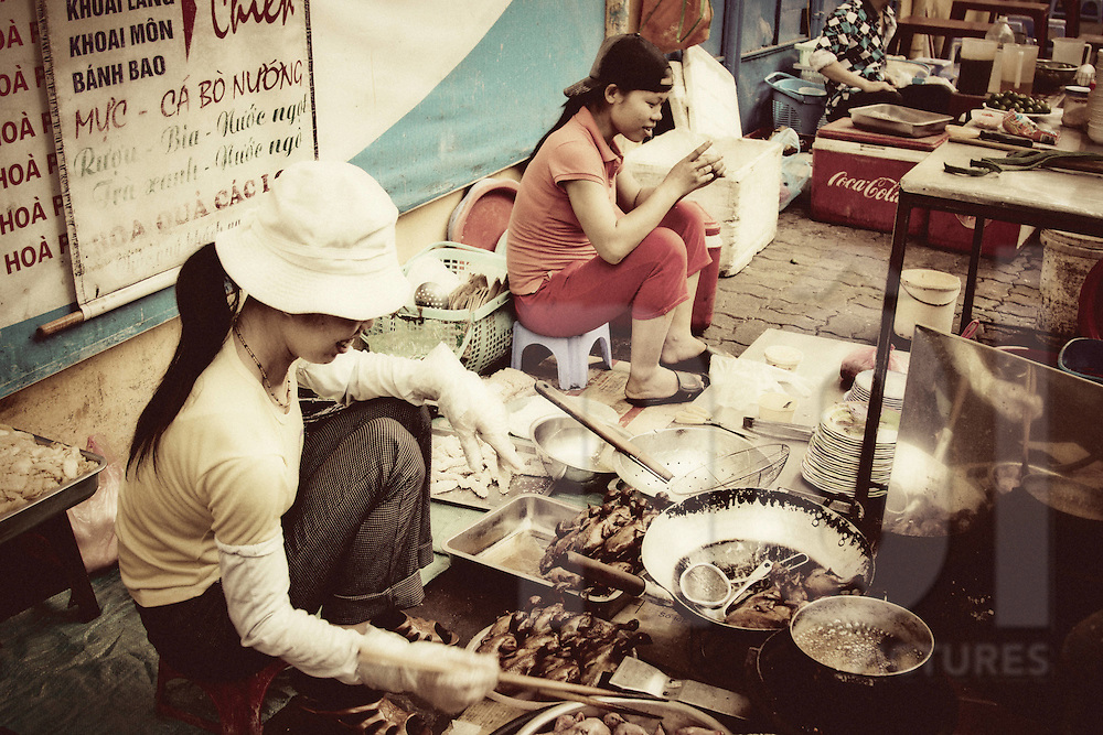 Food stall outside hang Day stadium, Cat Linh street, Hanoi, Vietnam, Asia. Vietnamese women cook roasted birds