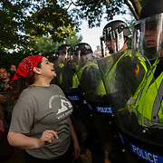 """Emily Filler attempts to dissuade state police from advancing on students rallying on the grounds of the University of Virginia on the second anniversary of the """"Unite the Right"""" rally in Charlottesville, W.V. on Saturday, August 11, 2018."""