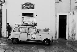 Reportage sviluppato ad Alessano (LE). Viene presa in considerazione fotograficamente, la gente che popola il paese nei suoi bar, piazze, strade, giardini pubblici. Ed, insieme a questa, i particolari caratterizzanti del luogo...Uomo sosta presso un'auto utilizzata per la campagna elettorale