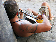 Young man with a tattoo relaxes on a beach playing a guitar.