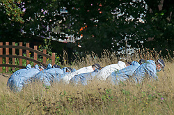 © Licensed to London News Pictures 21/09/2021. <br /> Kidbrooke, UK, Police search teams in forensic suits looking for evidence in the long grass at the scene. A Large police cordon is still in place around Cator Park at Kidbrooke Village in Kidbrooke, South East London today after the body of 28 year old school teacher Sabina Nessa was found near a community centre. Police believe Sabina was murdered by a stranger. Photo credit:Grant Falvey/LNP