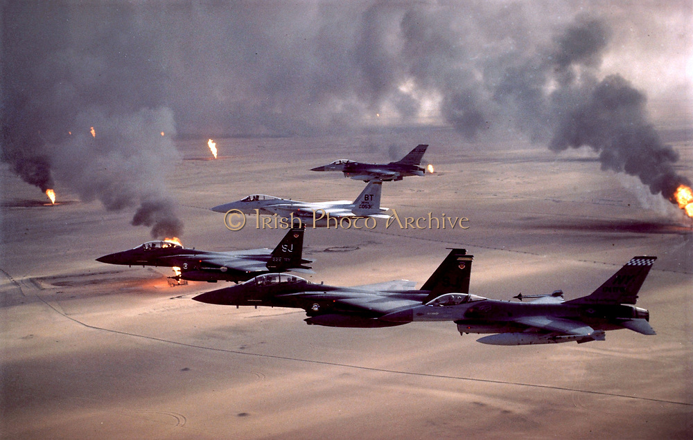 Operation Desert Storm (1991) F-16A Fighting Falcon, F-15E Strike Eagle, and F-15C Eagle fighter jets fly over Kuwait's burning oil fields. Photographer: Tech. Sgt. Fernando Serna, USAF