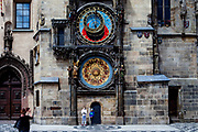 A mother is photographing her children which are wearing face-masks infront of the Prague Astronomical Clock, or Prague Orloj which is a medieval astronomical clock located at Old-Town Square in Prague, the capital of the Czech Republic. The Czech government lowered the security measures and as of Monday 25 May 2020, wearing of protective masks will be mandatory only in the interiors of buildings other than the place of residence and in public transport.
