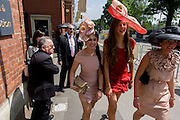 Wached by older men, three teenage girls smile as they walk through the high street during the annual Royal Ascot horseracing festival in Berkshire, England. Royal Ascot is one of Europe's most famous race meetings, and dates back to 1711. Queen Elizabeth and various members of the British Royal Family attend. Held every June, it's one of the main dates on the English sporting calendar and summer social season. Over 300,000 people make the annual visit to Berkshire during Royal Ascot week, making this Europe's best-attended race meeting with over £3m prize money to be won.