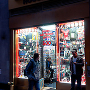 Tourist near electronics shop at night on Times Square, New York City